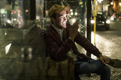 Portrait of laughing young man on the phone sitting at bus stop by night, Lisbon, Portugal - UUF19176