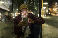 Portrait of smiling young man sitting at bus stop by night using cell phone, Lisbon, Portugal - UUF19179