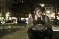 Portrait of happy young man using cell phone by night, Lisbon, Portugal - UUF19185