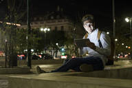 Portrait of young man using digital tablet and earphones in the city by night, Lisbon, Portugal - UUF19191