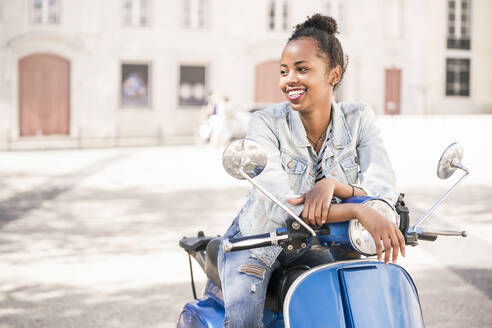 Happy young woman with motor scooter in the city, Lisbon, Portugal - UUF19200