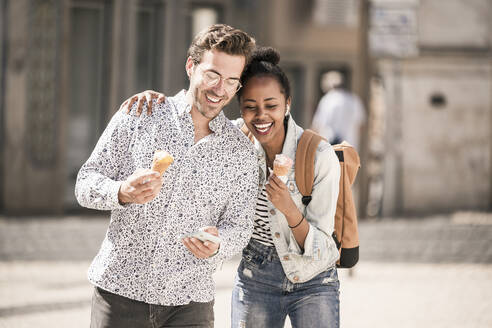Happy young couple with ice cream and mobile phone in the city on the go, Lisbon, Portugal - UUF19215
