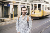 Smiling young man with backpack in the city on the go, Lisbon, Portugal - UUF19227