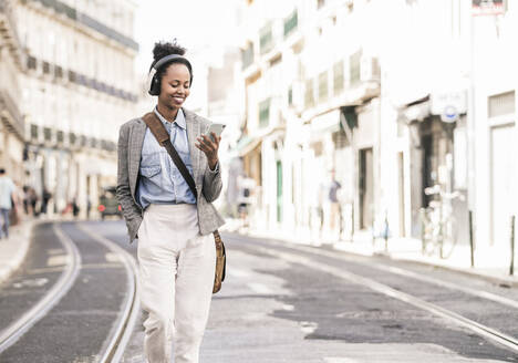 Smiling young woman with headphones and mobile phone in the city on the go, Lisbon, Portugal - UUF19230