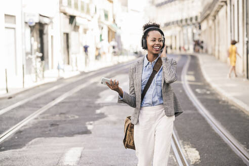 Happy young woman with headphones and mobile phone in the city on the go, Lisbon, Portugal - UUF19233