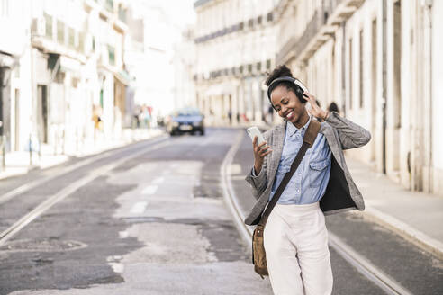 Happy young woman with headphones and mobile phone in the city on the go, Lisbon, Portugal - UUF19236