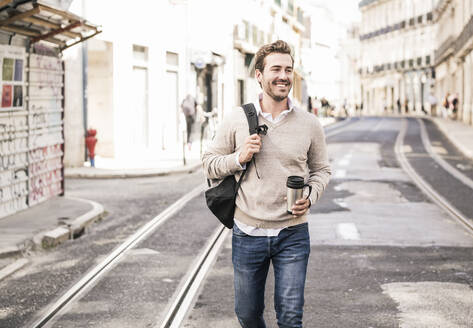 Smiling young man with backpack and coffee mug in the city on the go, Lisbon, Portugal - UUF19239