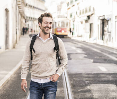 Happy young man with backpack in the city on the go, Lisbon, Portugal - UUF19242