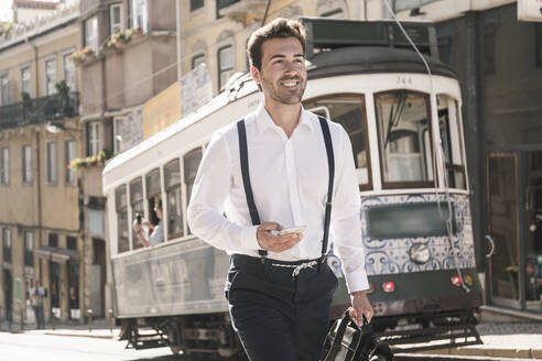 Smiling young businessman in the old town on the go, Lisbon, Portugal - UUF19251