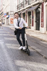 Happy young businessman riding e-scooter in the city, Lisbon, Portugal - UUF19257