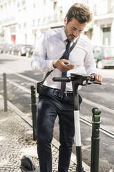 Young businessman with e-scooter using mobile phone in the city, Lisbon, Portugal - UUF19260