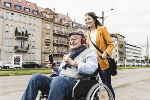 Smiling young woman pushing happy senior man with headphones and smartphone in wheelchair - UUF19272