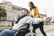 Laughing young woman pushing happy senior man in wheelchair - UUF19275