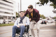 Young man pushing happy senior man in wheelchair - UUF19287