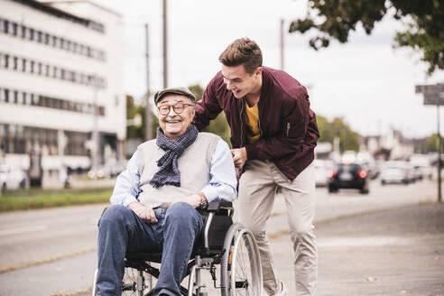 Young man pushing happy senior man in wheelchair - UUF19287