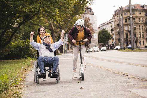 Senior man in wheelchair having fun with his adult grandchildren outdoors - UUF19302