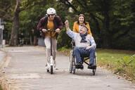 Senior man in wheelchair having fun with his adult grandchildren outdoors - UUF19305