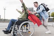 Young man pushing senior man sitting in a wheelchair dressed up as superhero - UUF19314