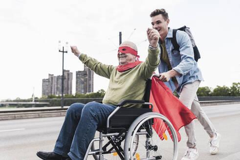 Young man pushing senior man sitting in a wheelchair dressed up as superhero - UUF19317