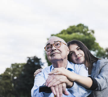 Portrait of senior man and his granddaughter in a park - UUF19338