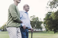 Senior man walking with help of his grandson in park - UUF19347