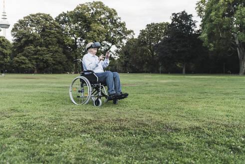 Senior man sitting in wheelchairin a park using Virtual Reality Glasses - UUF19350