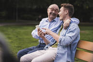 Senior man and grandson with smartphone sitting together on a park bench having fun - UUF19356