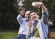 Senior man and grandson sitting together on a park bench taking selfie with smartphone - UUF19359