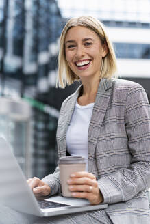 Portrait of happy young businesswoman with laptop in the city - DIGF08640