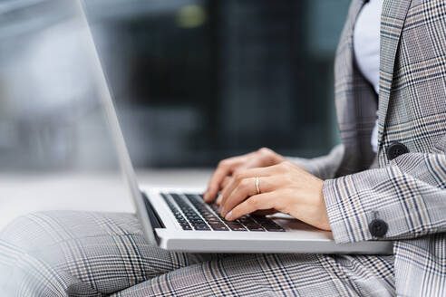 Close-up of businesswoman using laptop outdoors - DIGF08643