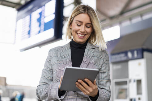 Smiling young businesswoman using tablet at the train station - DIGF08658