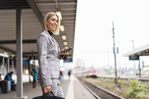 Smiling young businesswoman with mobile phone at the train station - DIGF08661
