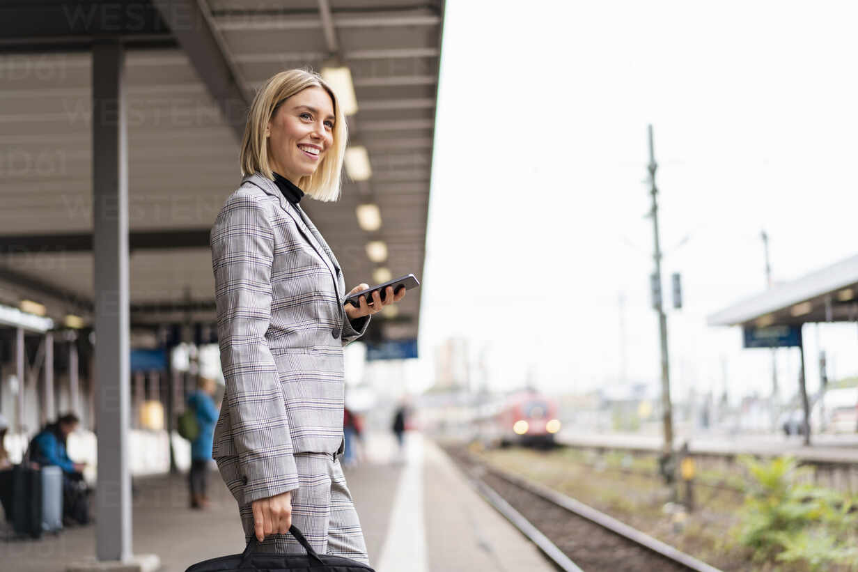Smiling young businesswoman with mobile phone at the train station - DIGF08661 - Daniel Ingold/Westend61