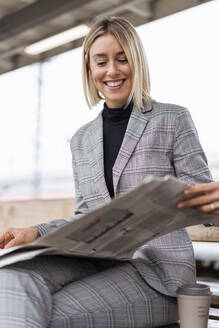 Smiling young businesswoman reading newspaper at the train station - DIGF08664