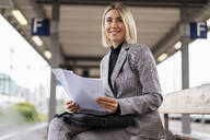 Smiling young businesswoman with papers at the train station - DIGF08667