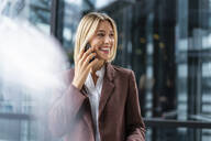 Happy young businesswoman on the phone in the city - DIGF08682