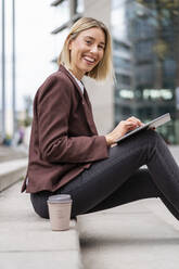 Portrait of happy young businesswoman using tablet in the city - DIGF08694