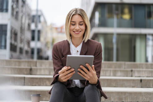 Smiling young businesswoman using tablet in the city - DIGF08697