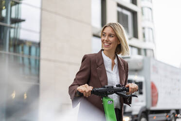 Happy young businesswoman with e-scooter in the city - DIGF08703