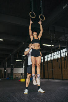 Young woman jumping to gymnastic rings, man helping her - MTBF00070