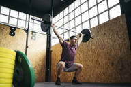 Young man doing overhead squat exercise at gym - MTBF00073