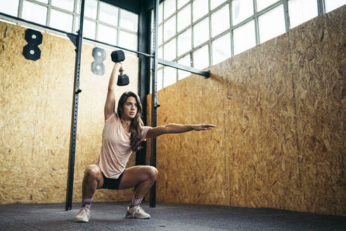 Young woman doing dumbbell exercise at gym - MTBF00076