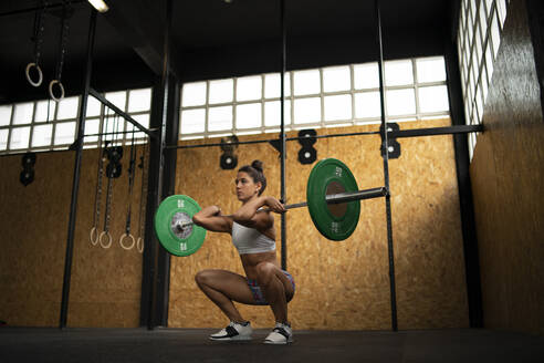 Young woman doing overhead squat exercise at gym - MTBF00082