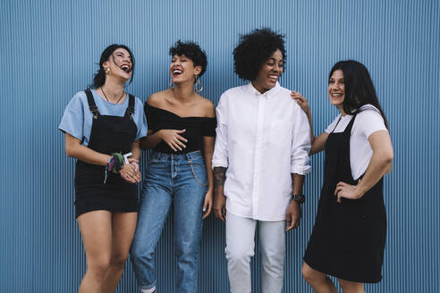 Laughing women in front of a blue wall - DAMF00209