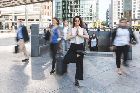 Young businesswoman practising yoga in the city at rush hour, Berlin, Germany - WPEF02181