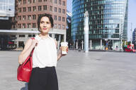 Young businesswoman with takeaway coffee in the city on the go, Berlin, Germany - WPEF02184