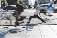 Young businesswoman practising yoga in the city at rush hour, Berlin, Germany - WPEF02190
