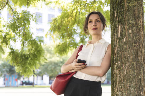Young businesswoman with cell phone in a park - WPEF02196