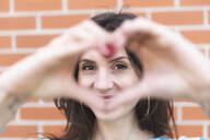 Portrait of smiling young woman looking at camera through heart-shaped hands - WPEF02199