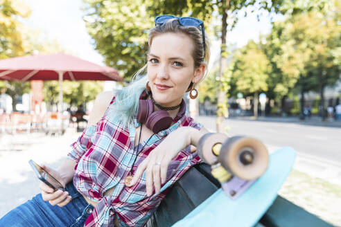 Portrait of smiling young woman sitting on bench with skateboard and smartphone - WPEF02205
